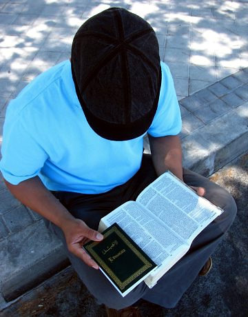 S. Benaessa lee la Biblia sin mostrar su rostro por temor a las represalias por su apostasía